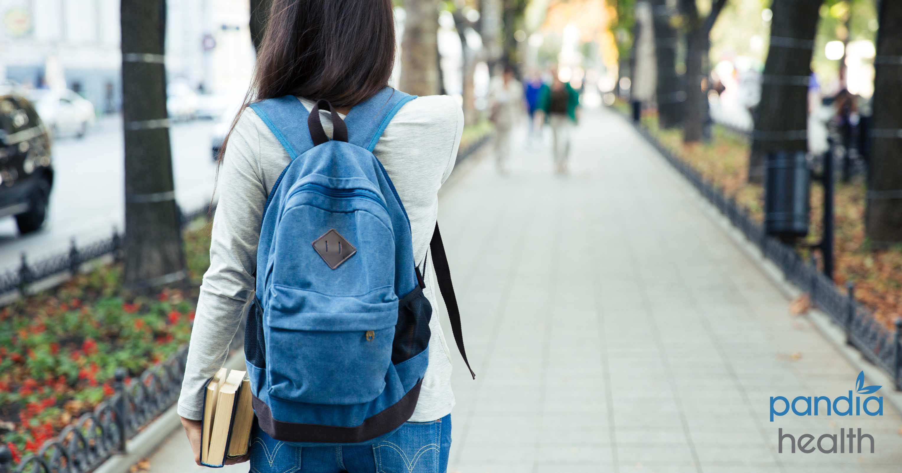Woman walking with backpack and holding books