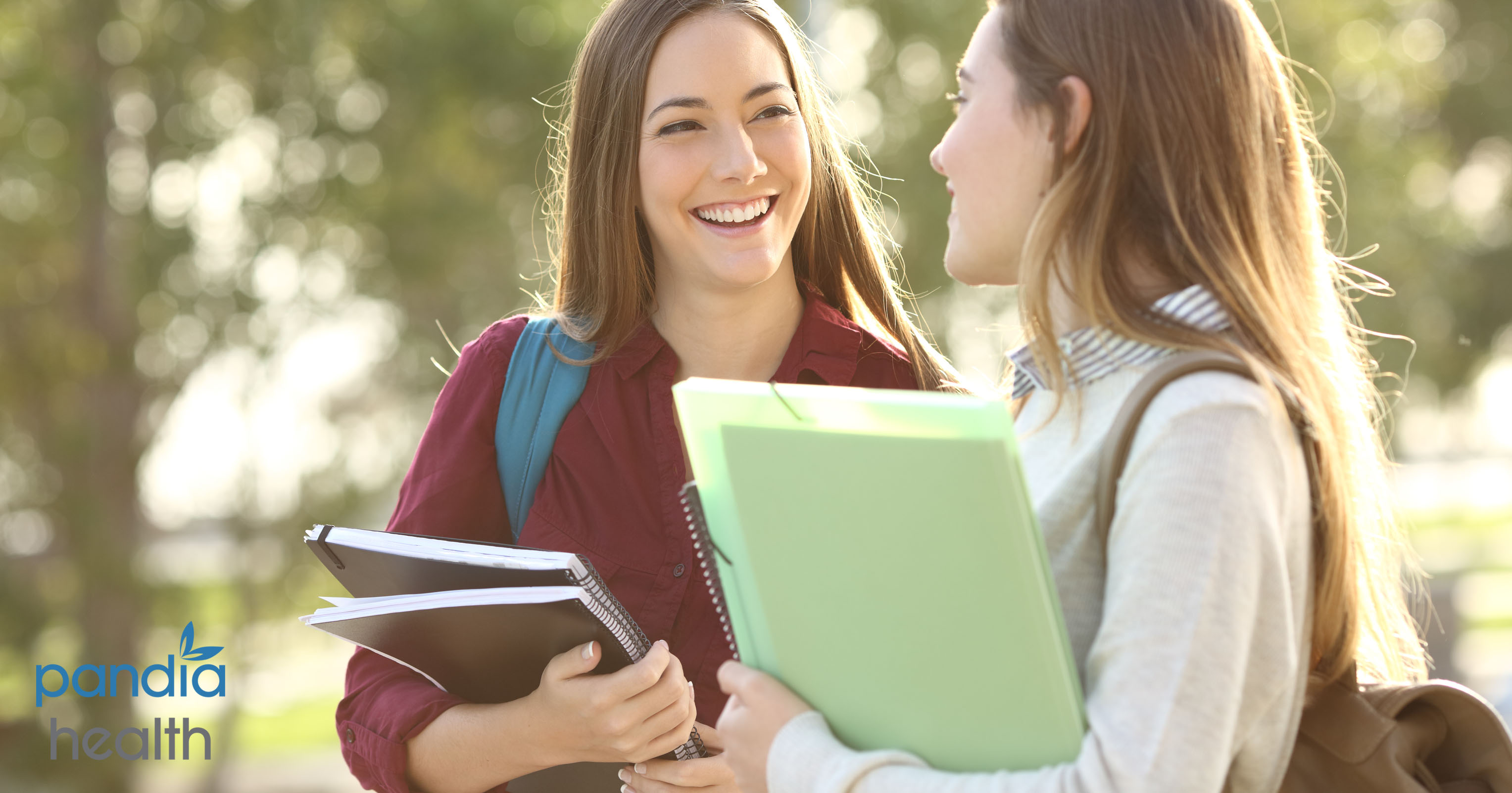 Two school girls holding notebooks and laughing