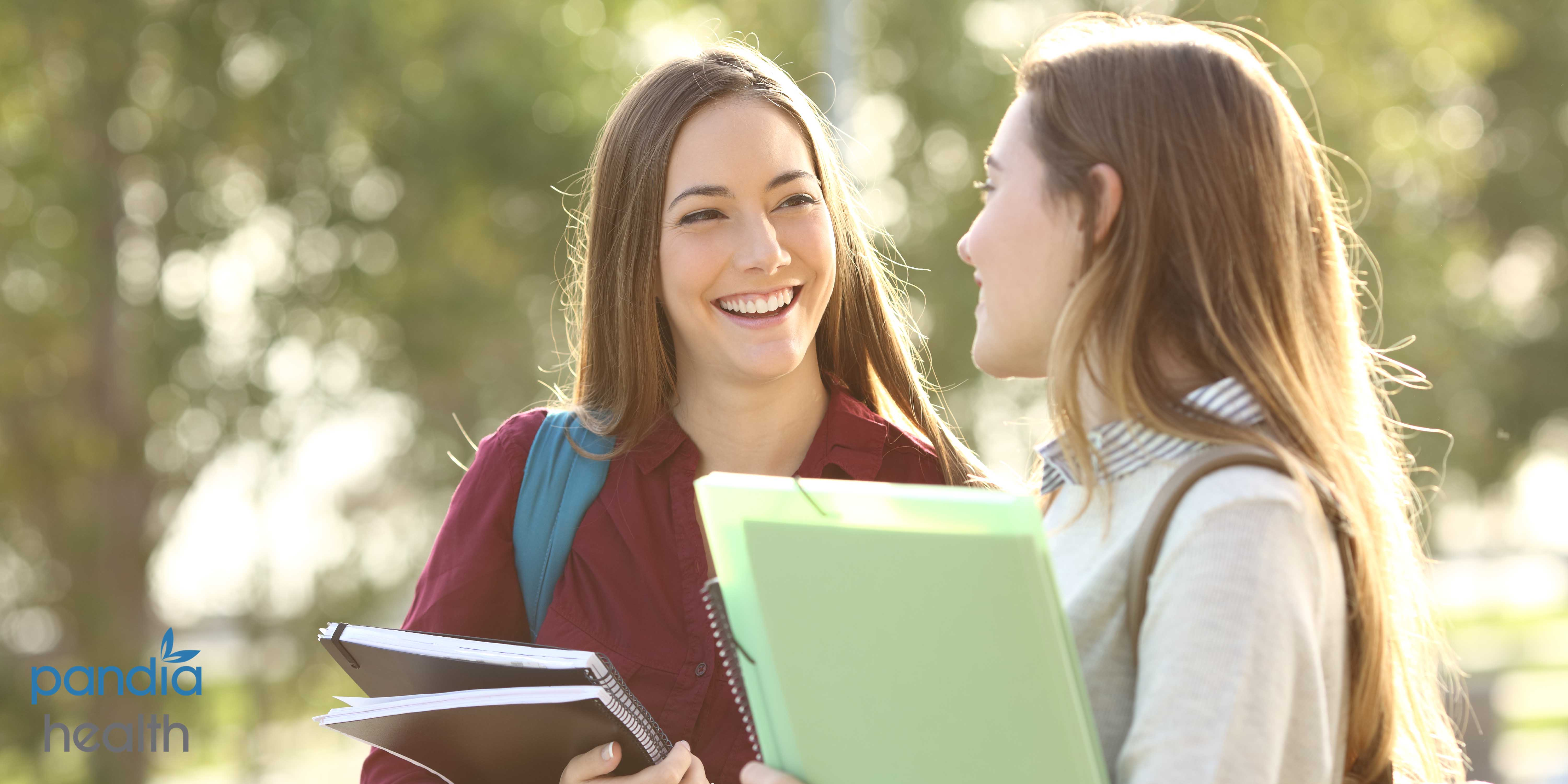 Two schoolgirls holding notebooks and laughing