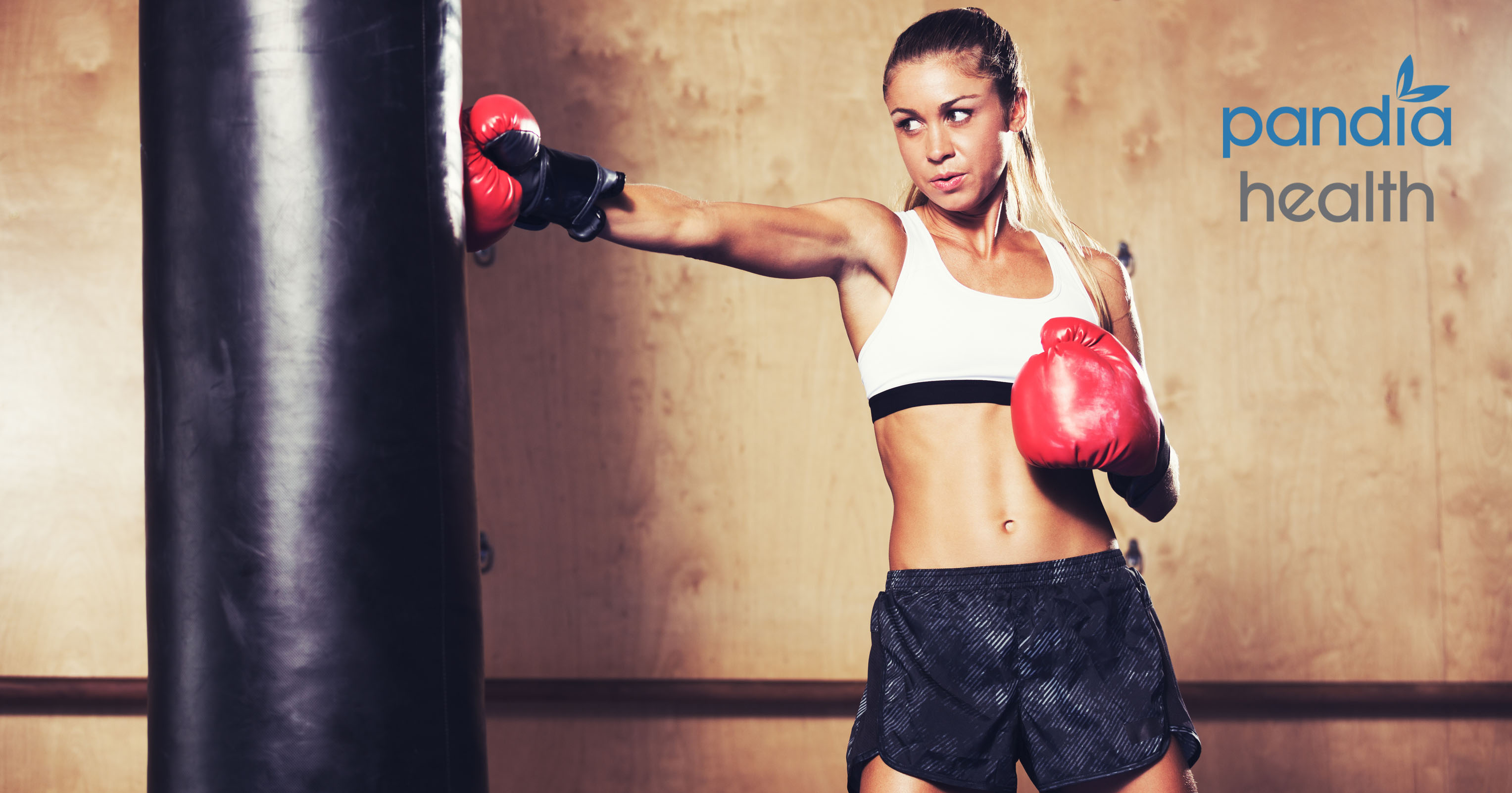 Woman in kickboxing gloves punching bag