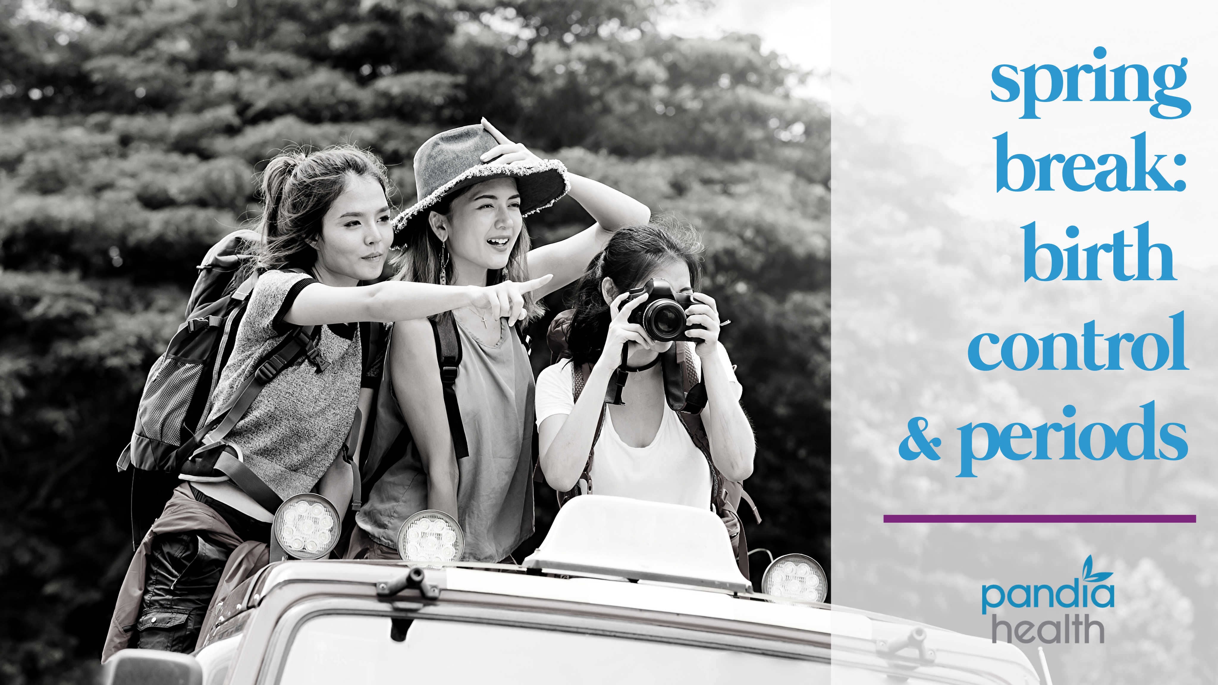 three girls standing up out of a jeep in travel clothes, one pointing and one taking a photo, all smiling, in black and white