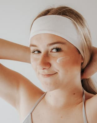 Woman Using Acne Cream on Face
